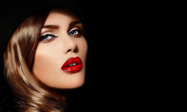 大きな黒い帽子で完璧なきれいな肌と、赤い唇と明るい化粧品で美しいセクシーなスタイリッシュな白人若い女性モデルのファッション性の高いlook.glamorのクローズアップの肖像画