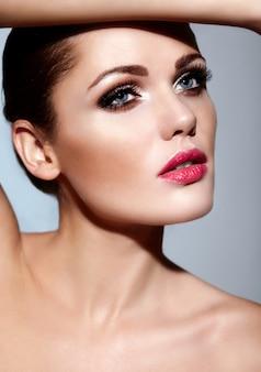 ピンクの唇、完璧なきれいな肌と明るいメイクと美しいセクシーな白人若いブルネットの女性モデルのファッション性の高いlook.glamorのクローズアップの肖像画