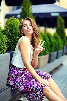 ファッション性の高いlook.glamourスタイリッシュなセクシーな笑みを浮かべて美しい官能的な若い女性モデルで夏の明るい通りで流行に敏感な服