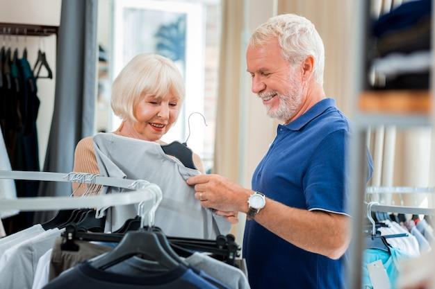 ここを見て。 tシャツを手に持って興味を示しながら喜びを表現する集中老夫婦