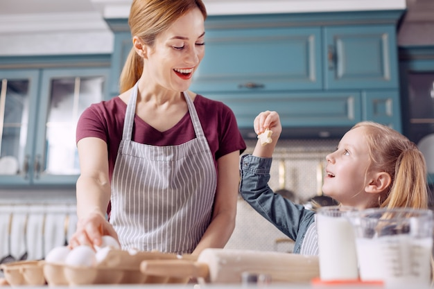 Look here. cute little girl showing her mother a star-shaped cookie, having made it by herself, while helping her mother with cookie-baking