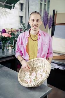 ここを見て。彼の顔に笑顔を保ち、結婚披露宴のために花びらを準備するハンサムな男性の人