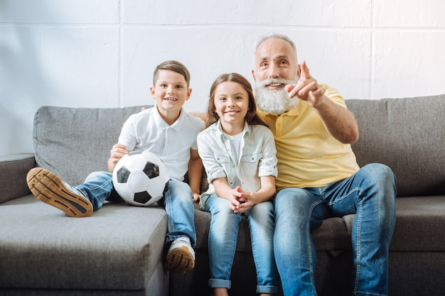 Look here. pleasant elderly man with a grey beard sitting on the sofa next to his little grandchildren, watching football game highlights with them and pointing at the best players