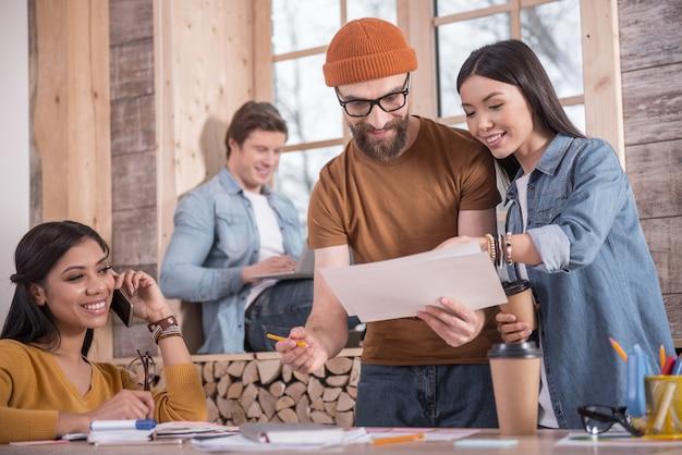 Смотри сюда. позитивно довольная молодая женщина, стоящая вместе со своим коллегой и указывая на рисунок, предлагая свои идеи
