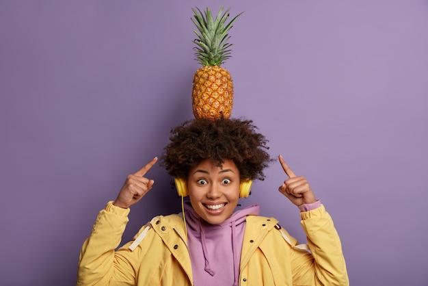 Guarda come posso! la donna afroamericana dell'adolescente allegro positivo indica l'ananas sulla testa, ascolta l'audio in cuffia, indossa una felpa con cappuccio e una giacca, isolato sopra il muro viola, si diverte da solo
