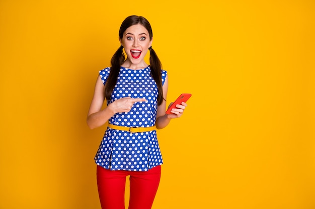 Look i found social media promo. excited crazy girl use smartphone point index finger indicate sales wear trendy trousers isolated over bright shine color background