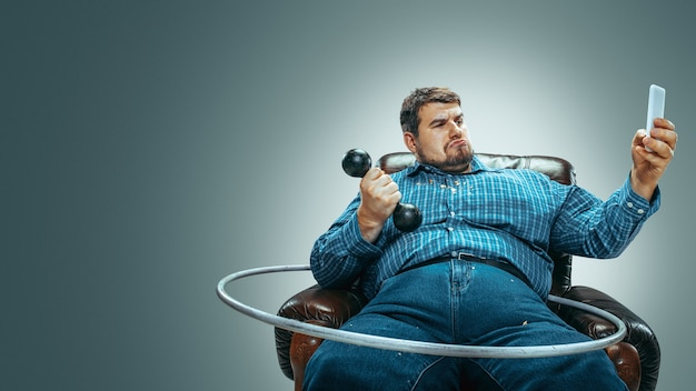 내가 낚시를 좋아해. 회색 배경에 갈색 안락의자에 앉아 있는 뚱뚱한 백인 남자의 초상화. 훈련 무게와 후프로 셀카 만들기. 과체중, 근심 없는. 체중 감량의 개념입니다.