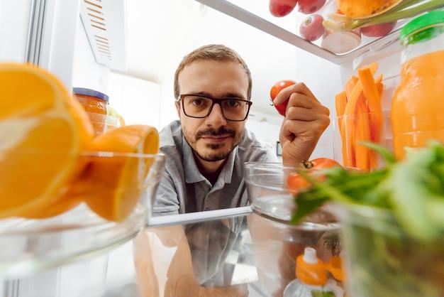 Загляни в холодильник. молодая и успешная влюбленная пара заглядывает в холодильник и достает из холодильника бутылку молока, стоя на кухне и готовит завтрак.
