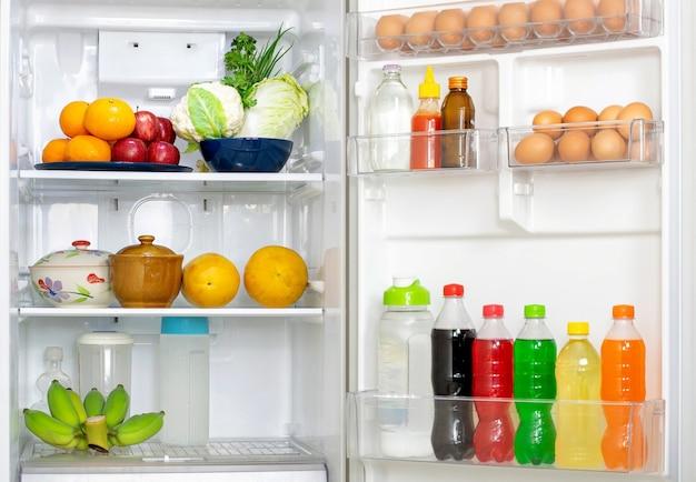 蓋を開けて冷蔵庫を覗き込むと、中にたくさんの生鮮食品や飲み物が入っています。