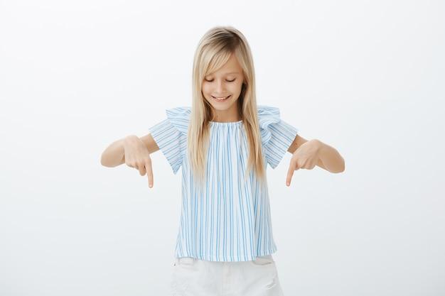 ほら、すごい。ブロンドの髪を持つ好奇心旺盛なスマートな女の子、指差しして見下ろして、広く笑って、階下を見ながら夕食を作っているお母さんと話しながら興味をそそられる
