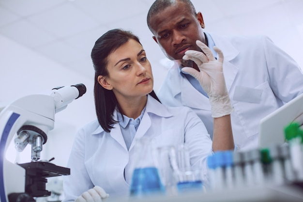 Look at it. unsmiling experienced researcher looking at a sample and her colleague standing behind her