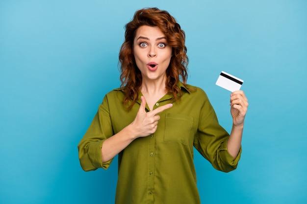 その信じられないほどの驚いた女性のホールドポイントの人差し指のクレジットカードを見てください青い色の背景の上に分離された簡単な支払いの銀行サービスの着用スタイルのスタイリッシュな服に感銘を受けました