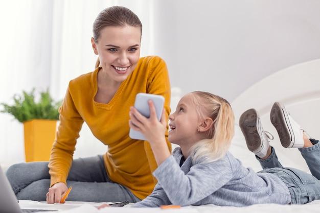 お母さん見て。かわいい娘が彼女の携帯電話を見せて笑っている間、画面を見ている陽気なエネルギッシュな母親