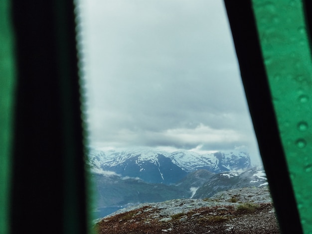 Look at mountains covered with snow through the tent