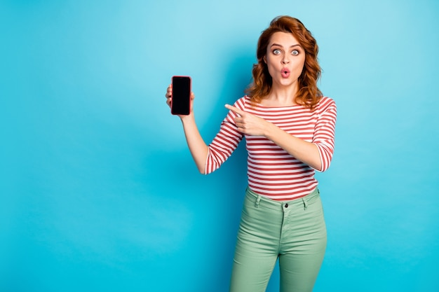 Look new modern device! astonished crazy woman hold smartphone point index finger indicate unbelievable ads promotion impressed scream wow omg wear pullover isolated blue color