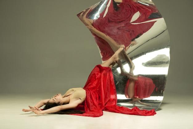 情熱の表情。鏡付きの茶色の壁にモダンなバレエダンサー。表面での錯覚の反射。柔軟性、動きの魔法。パラレルドリームワールド。クリエイティブアート、アクション、インスピレーションのコンセプト。