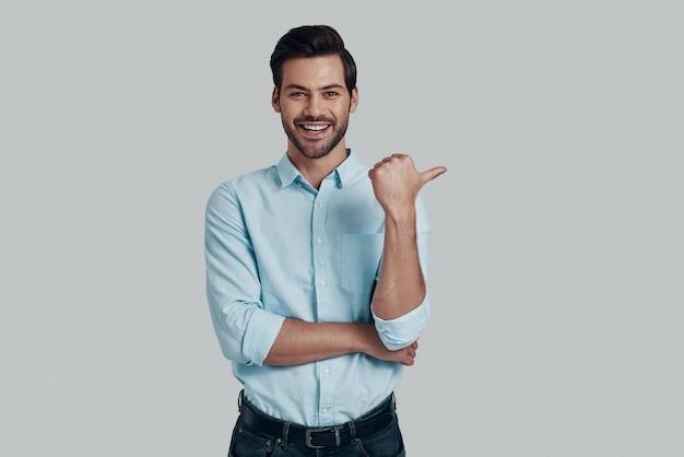 向こうを見て!笑顔でカメラを見て、灰色の背景に立っている間コピースペースを指しているハンサムな若い男