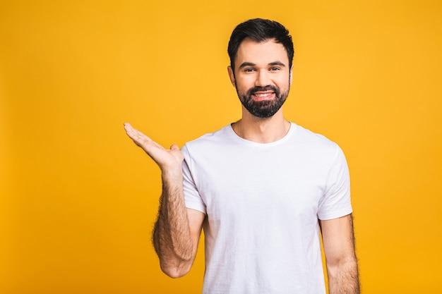向こうを見て!コピースペースを指差して、黄色の背景の上に孤立して立っている間笑顔でカジュアルに幸せな若いハンサムな男。