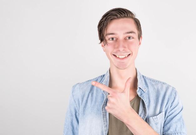 向こうを見てください白い背景に立っている間、離れて指し、笑顔のジーンズシャツの幸せな若いハンサムな男