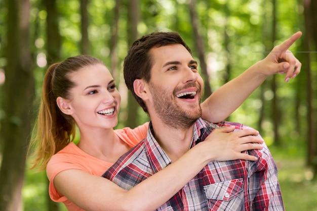 저기 봐! 여자가 남자를 껴안고 미소로 가리키는 동안 공원에서 산책하는 행복한 젊은 사랑의 커플
