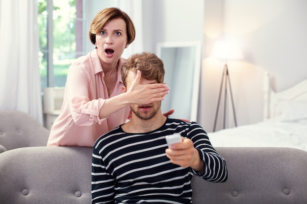 Do not look. shocked aged woman covering her sons eyes while controlling what he is watching