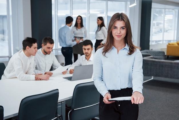 カメラをまっすぐ見てください。バックグラウンドで従業員とオフィスに立っている若い女の子の肖像画