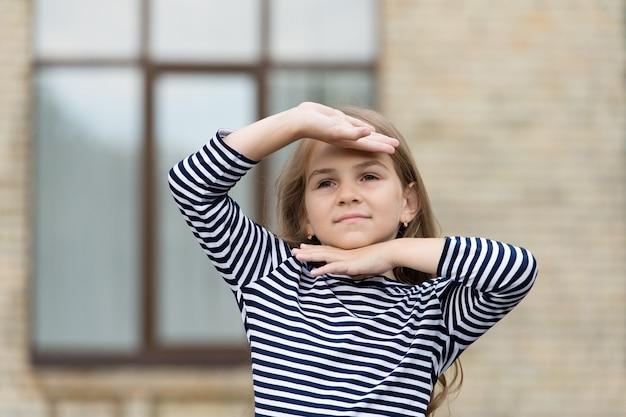 印象に残る表情。小さな子供は屋外の都会の顔の周りに手を握ります。美貌。小さな女の子のファッションルック。美容院。スキンケアとヘアケア。子供服。ベビーストア。
