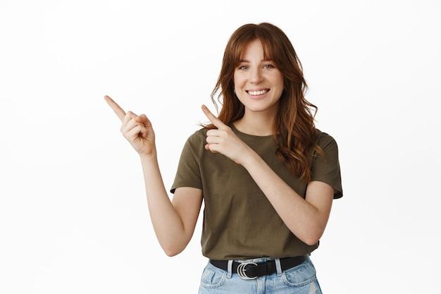 Смотри сюда. улыбающаяся счастливая молодая женщина представляет логотип компании, указывая пальцами в левый верхний угол и выглядит дружелюбно, стоя на белом