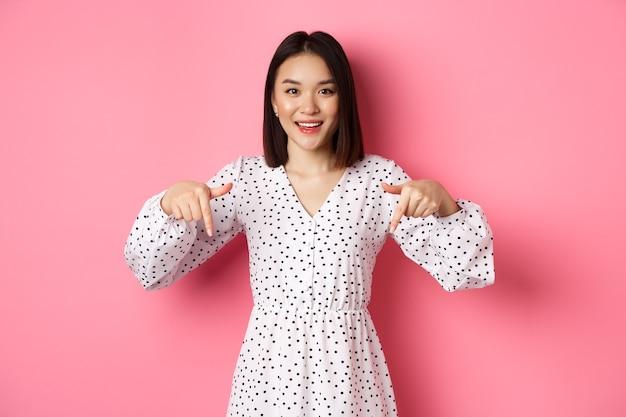 Guarda qui. carina donna asiatica in abito, che punta le dita verso il basso nello spazio della copia, mostra lo sconto del prodotto e sorride, in piedi su sfondo rosa