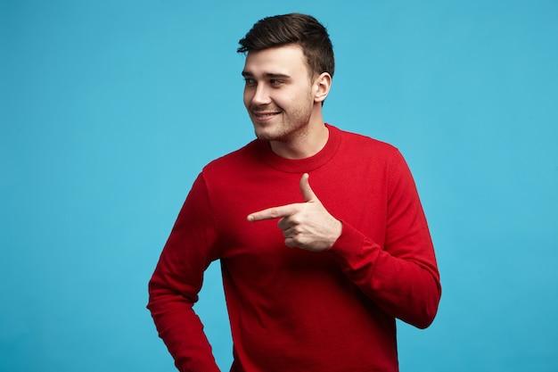 Guarda là! felice giovane attraente con stoppie in posa contro la parete in bianco dello studio blu