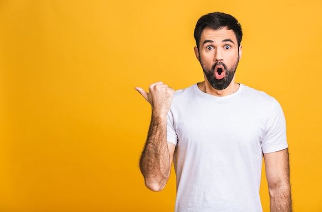 Look over there! happy young handsome man in casual pointing away at copyspace and smiling while standing isolated over yellow background.
