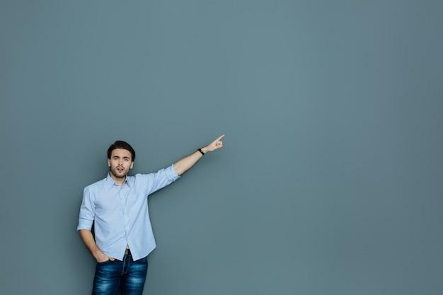 あっち見て。壁に孤立して立って、あなたを見ながら彼の手で指している楽しい感情的なハンサムな男