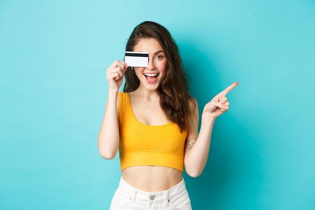 저길 봐. 플라스틱 신용 카드를 보여주는 세련된 현대 여성, 웃고 오른쪽을 가리키며 배너 또는 로고로 가는 길을 보여주며 파란색 배경에 서 있습니다.