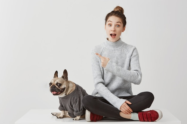 Look there! surprised woman pointing index finger asking for paying attention on something worthy. female model gesturing meaning this is cool in company of dog. lifestyle concept, copy space