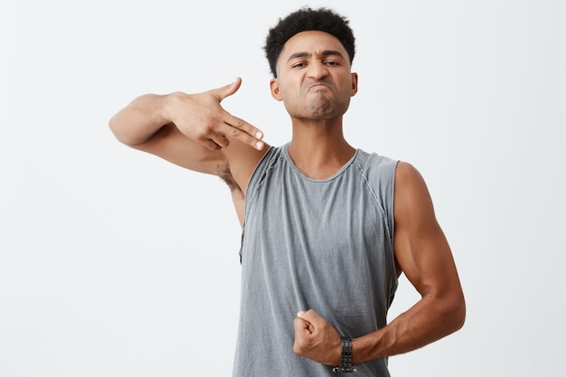 Look at this body. portrait of young dark-skinned serious man with afro hairstyle showing gun gesture with hand, pointing at his muscles with mean face expression.