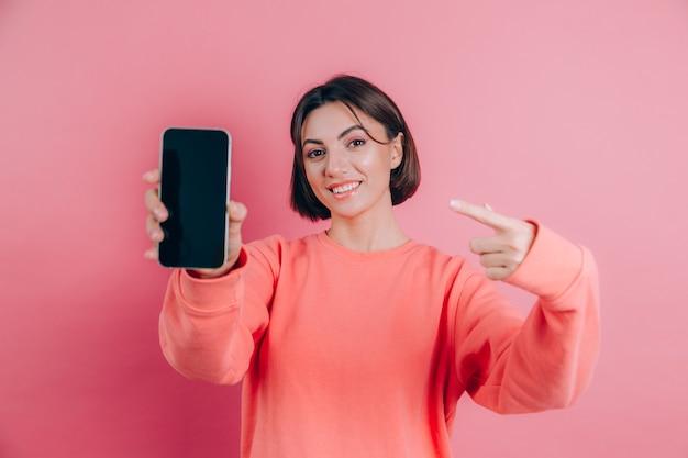 Guarda questo cellulare! la donna felice soddisfatta indica con il dito indice allo schermo vuoto, mostra il dispositivo moderno, emozioni sorprese felici.
