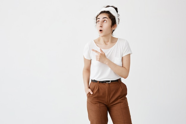 Look at this! cheerful young dark-haired woman with hair bun popped eyes in excitement, pointing her index finger away, indicating copy space on white blank wall for promotional information