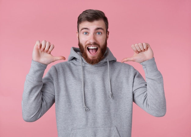 Look at this cool guy! young handsome positive red bearded man in gray hoodie, looks happy and broadly smiles, stands over pink background and pointing at himself.