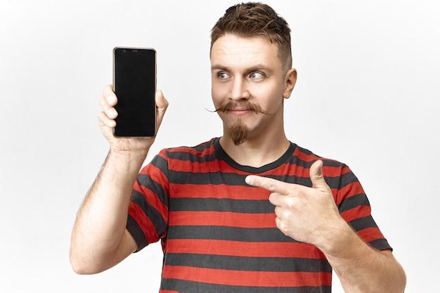Guarda questo. bello giovane commesso emotivo con elegante barba e baffi in posa in studio con smart phone in mano, puntando il dito contro lo schermo vuoto copyspace, presentando gadget