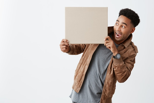 Look at this. isolated on white portrait of dark-skinned funny guy with afro hairstyle in casual winter clothes holding cardboard in hands, looking at it with opened mouth and shocked expression.