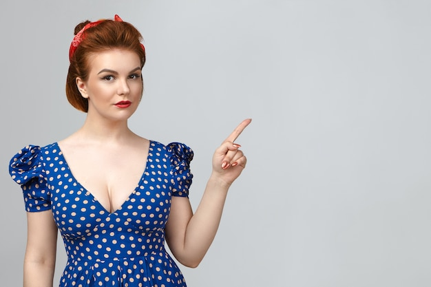 Look at this. picture of gorgeous young caucasian pin up woman wearing bright make up and low neck retro dress pointing fore finger, demonstrating advertising content on blank gray studio wall