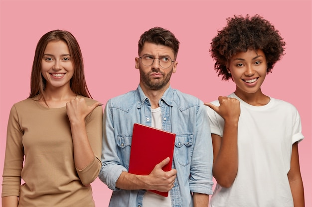 Look at this wonk! cheerful women point with thumb at guy who stands between them