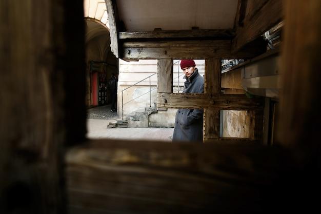 Посмотрите деревянные блоки на молодого человека в сером пальто