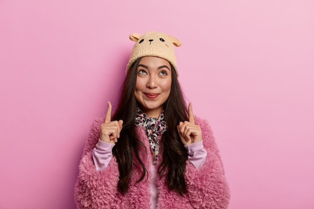 見上げる。魅力的なブルネットの女性は人差し指を上向きにし、心地よい優しい笑顔でクールなアイテムをデモンストレーションし、ピンクのコートを着ています