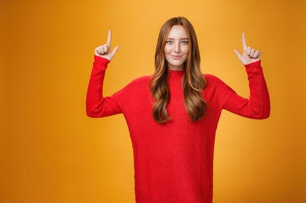 후회하지 마시고 찾아보세요. 위쪽을 가리키는 빨간 니트 드레스를 입고 주황색 배경 위에 자신만만한 미소를 지으며 자신 있게 웃고 있는 자신감 있고 세련된 20대 젊은 빨간 머리 여성의 초상화