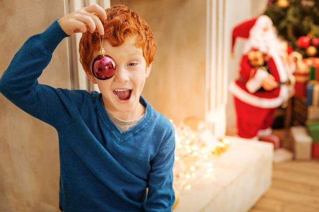 私がしていることを見てください。魅力的な縮れ毛の子供は彼の感情を中に保ち、クリスマスツリーの赤いボールで遊ぶことができません