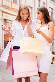 Посмотри, что у меня есть! красивая молодая женщина показывает своей подруге, что у нее есть в сумке для покупок, пока оба стоят на открытом воздухе