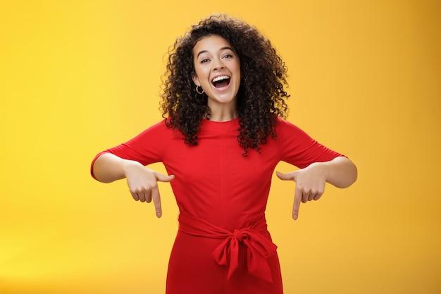 私がここで得たものを見てください。赤いドレスを着た巻き毛のカリスマ的な屈託のない幸せな魅力的な女性は、黄色い壁の上の顧客に素晴らしいコピースペースを見せているように下向きに広い笑顔で笑っています。