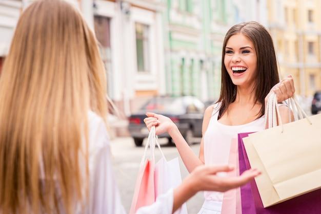 내가 뭘 얻었는지 봐! 쇼핑백을 들고 얼굴을 맞대고 몸짓을 하는 두 젊은 여성