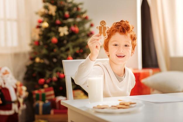 Посмотри, что у меня есть. сияющий рыжий ребенок с широкой улыбкой на лице показывает домашнее имбирное печенье и наслаждается рождественскими праздниками.